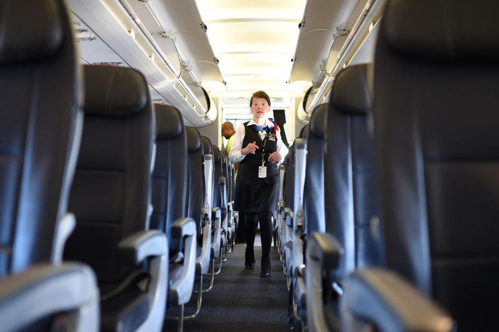 checks the passengers' seats for forgotten items