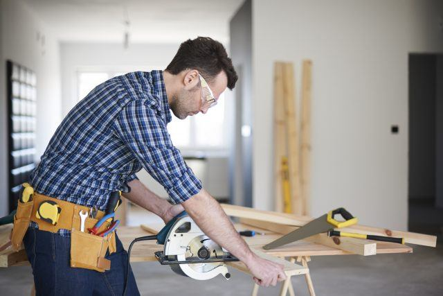 Construction worker or contractor using a saw