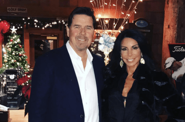 Danielle Staub and Marty Caffrey posing in front of a Christmas tree.