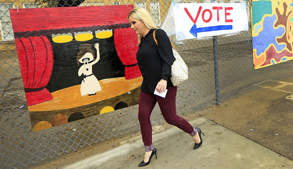 Voter Christi Selleck passes by a handmade voting sign in Fort Worth, Texas