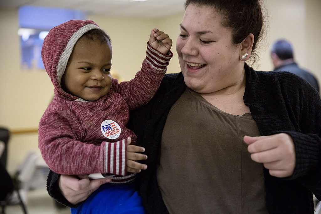 Hayley Bruneau receives a sticker after casting her vote with son Tayvin Faris, 1, at the Immaculate Conception Church on November 8, 2016, in Penacook, New Hampshire