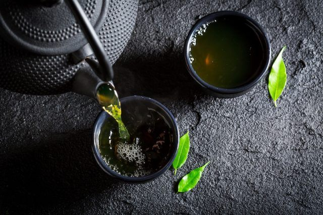 Delicious green tea with teapot and cup on black rock