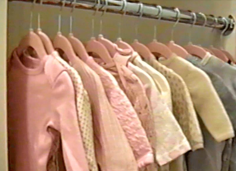 Baby clothes hanging in a closet