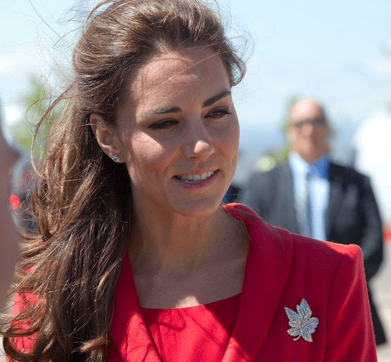 Kate Middleton wears a red dress with a brooch