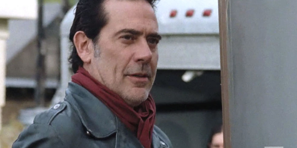 Negan looks ahead while wearing a black jacket and red scarf