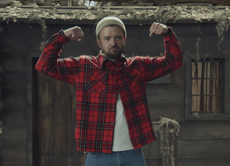 Justin Timberlake flexes his arms in a flannel shirt