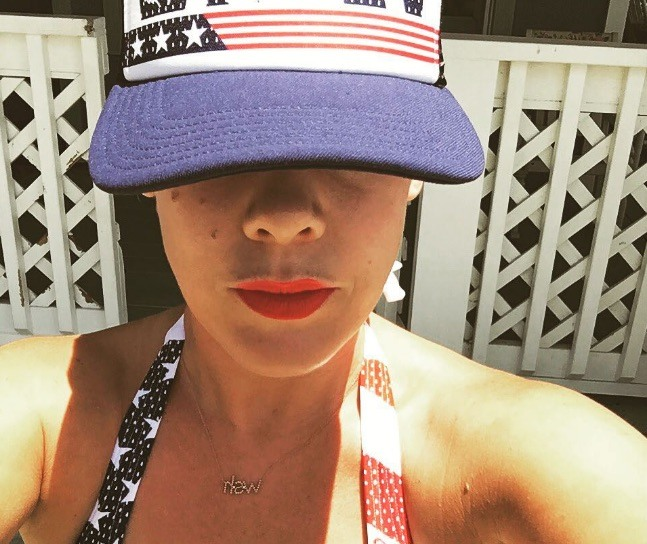 Pink wearing an American flag hat and swimsuit