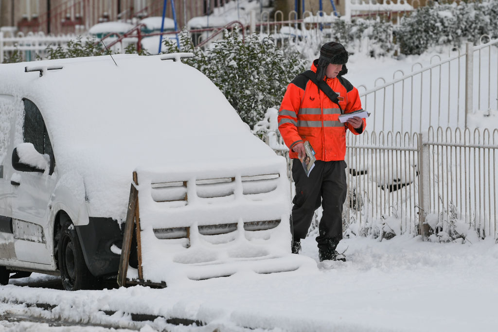A postman makes his way through the snow