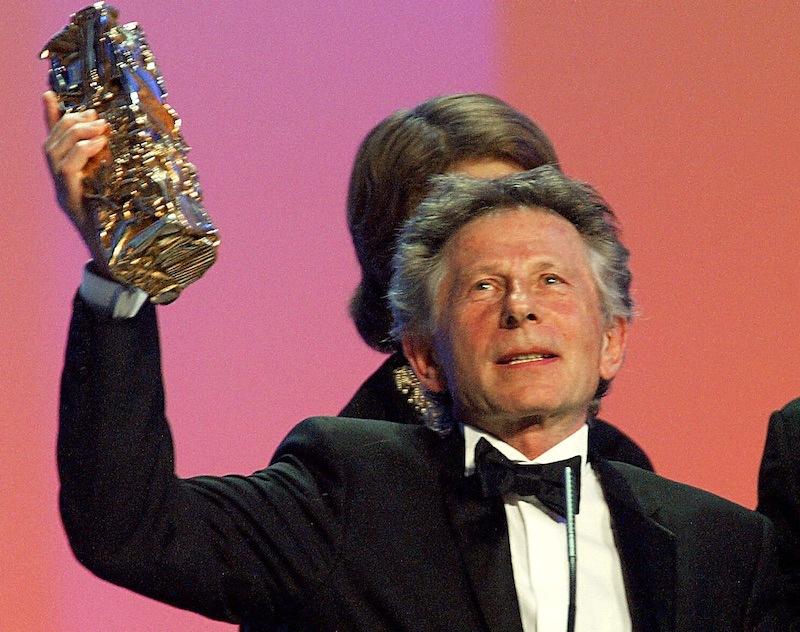 Roman Polanski holds up an award