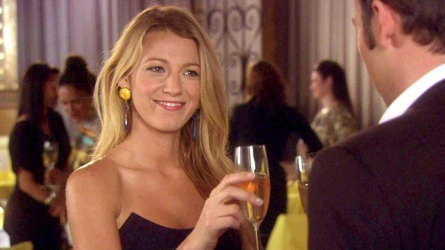 Blake Lively holding a glass of champagne in 'Gossip Girl'.