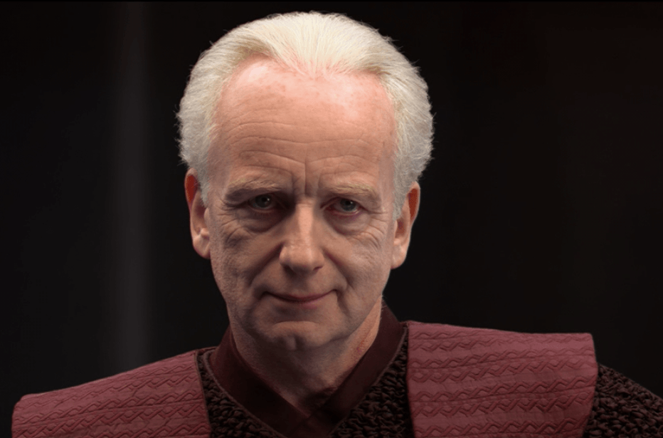 Sheev Palpatine smiling slightly while wearing red clothing,