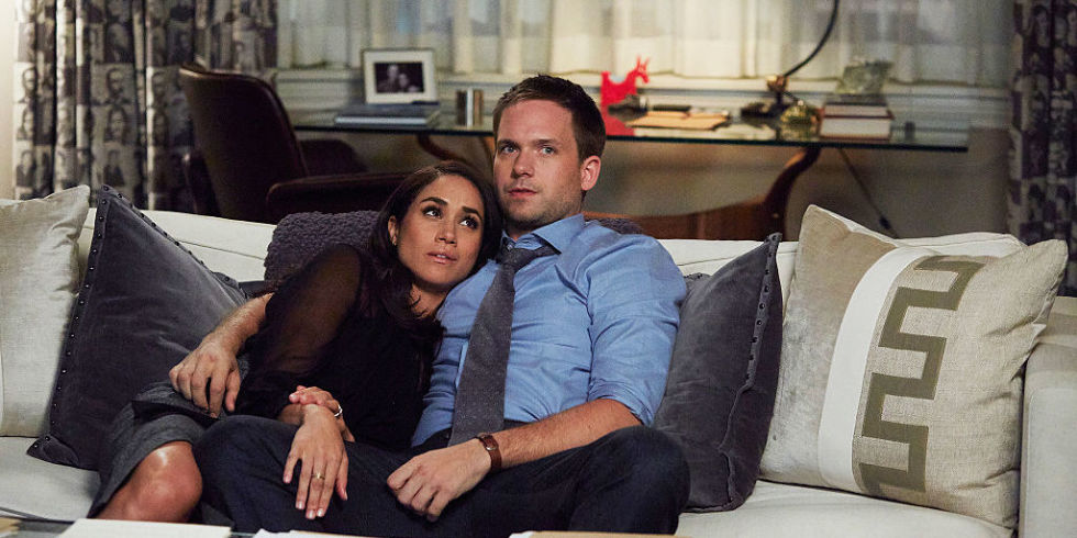 Meghan Markle and Patrick Adams sit on a couch on Suits