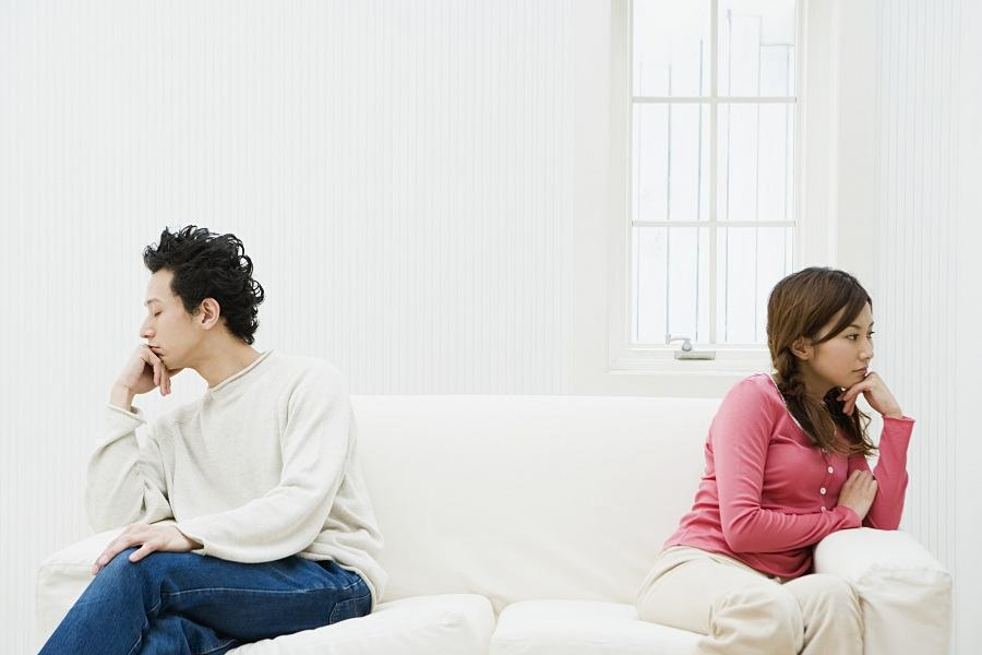 unhappy couple sitting on opposite sides of the couch