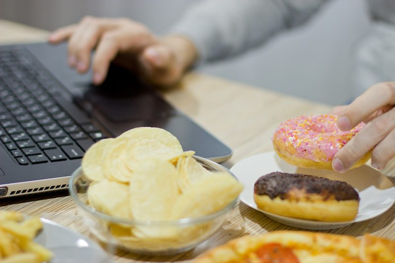 A man works at a computer and eats fast food. unhealthy food: Burger, sauce, potatoes, donuts,chips.
