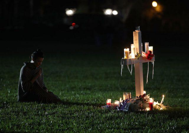 A mourner sits in front of a white cross.