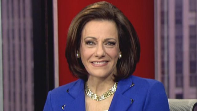 K.T. McFarland smiles while wearing a blue jacket and gold jewelry