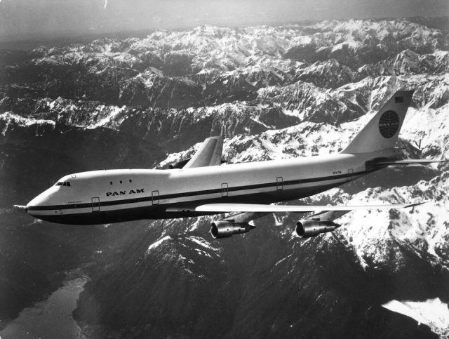 A Pan Am boeing 747 flying over snow covered mountains