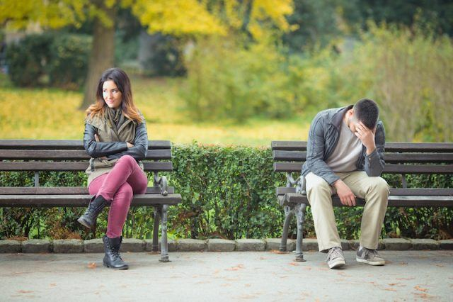 A woman sits happily while a man looks upset on the bench over.