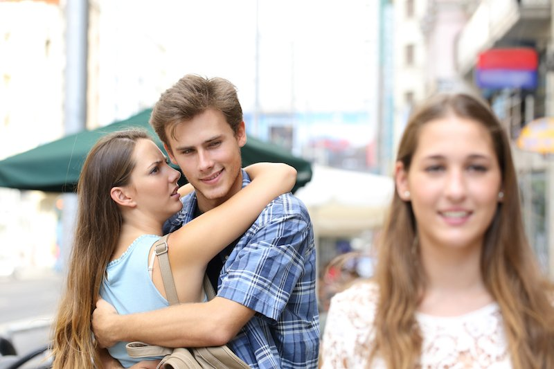 Unfaithful man hugging his girlfriend and looking another