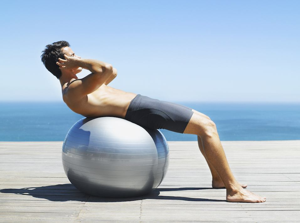 Man doing sit-ups with an exercise ball