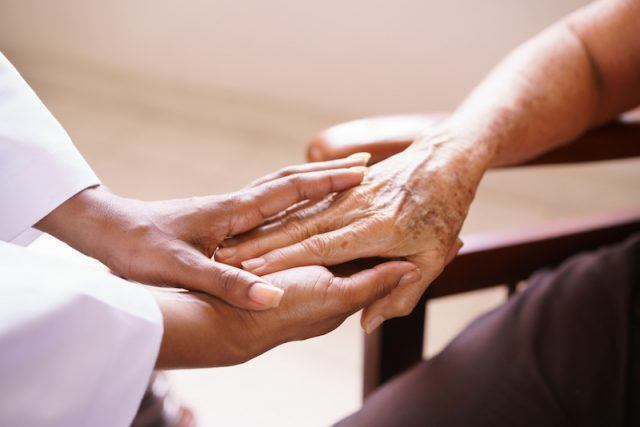 A woman holding hands with an elderly patient.