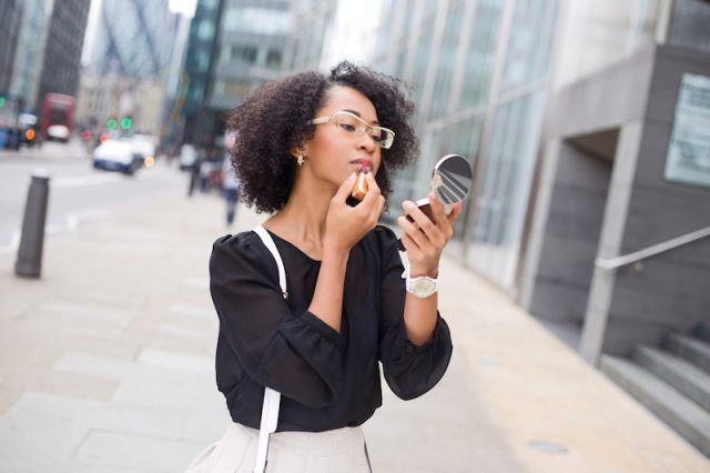 A woman applies lipstick with a compact mirror.