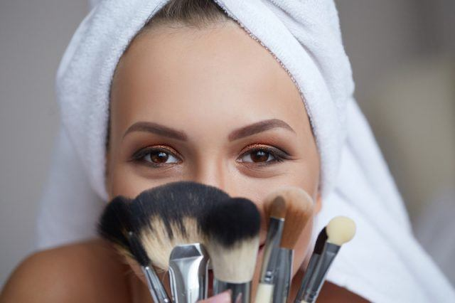 A woman holds up makeup brushes.