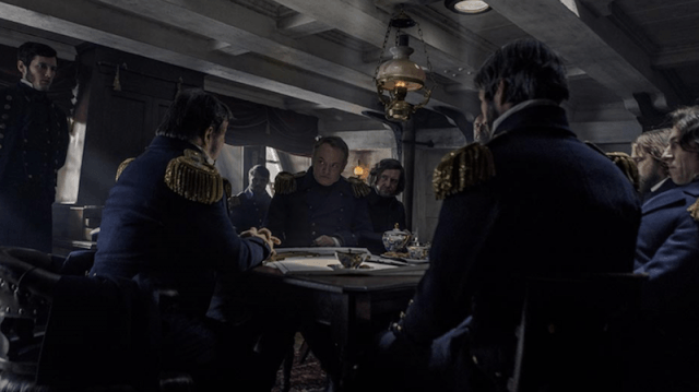 A group of men sitting inside a room in the ship.