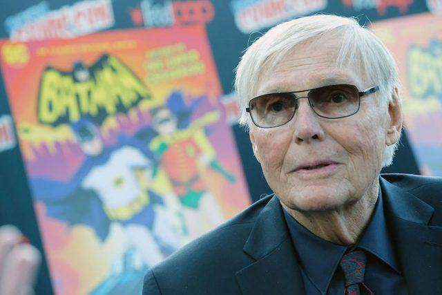 Adam West in front of a Batman poster.