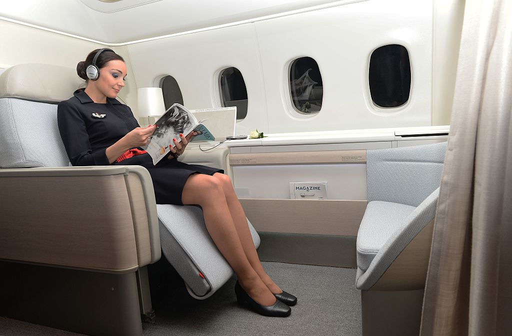 "An Air France attendant shows off the airline's ""haute couture"" suite featuring a seat that reclines into a bed"