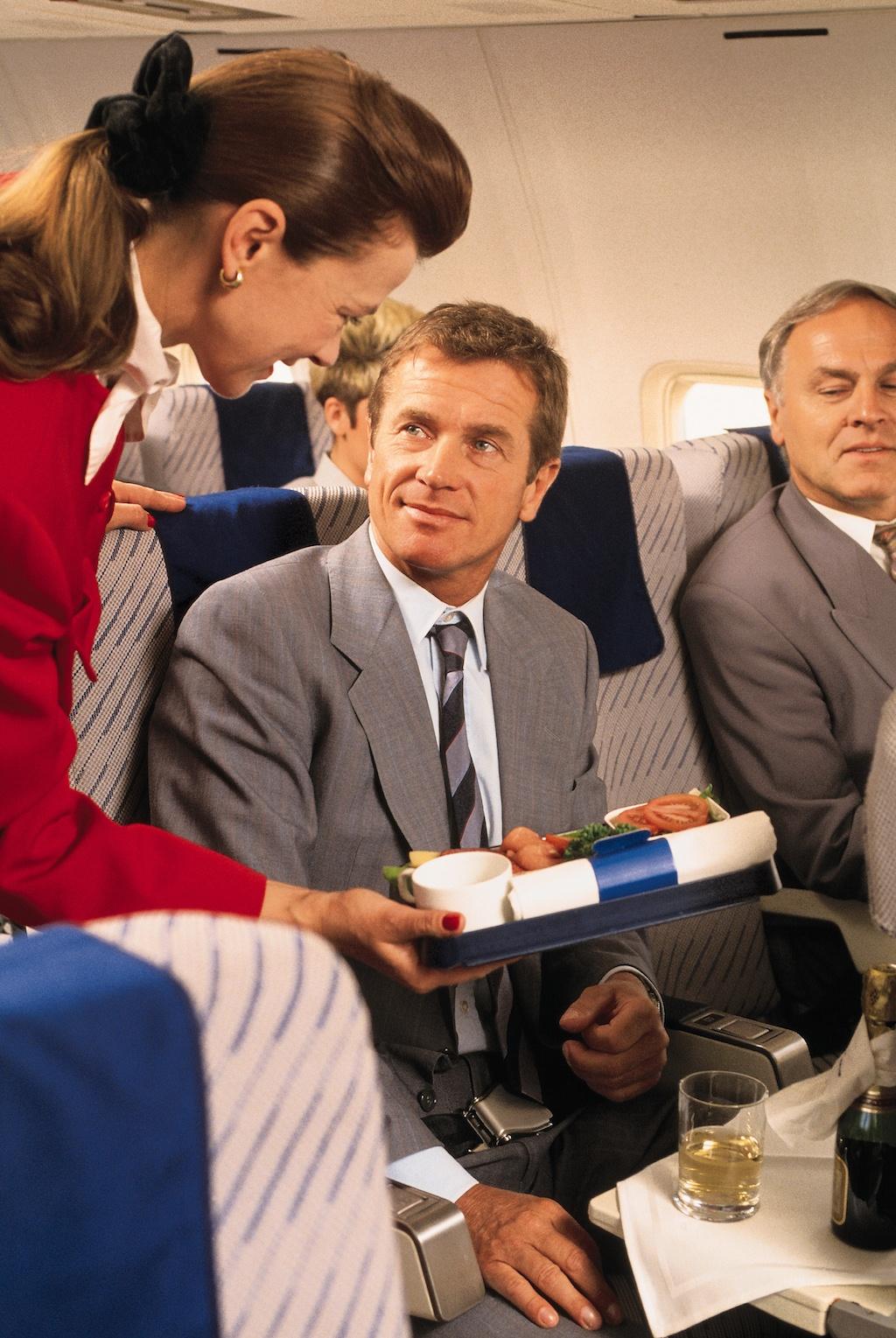 Flight attendant helping businessman on airplane