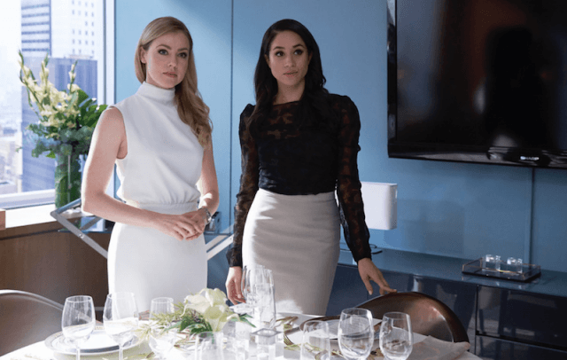 Amanada Schull stands with Meghan Markle in a conference room in 'Suits'.