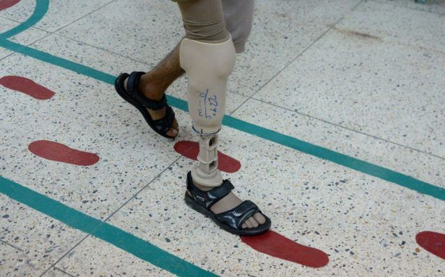 An Afghan amputee walks with a prosthetic leg at a International Committee of the Red Cross