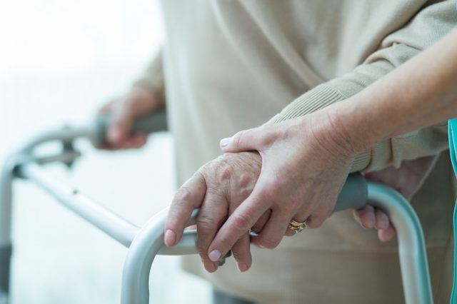 An elderly patient being assisted on a walker.
