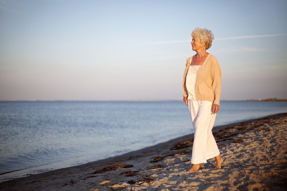 woman walking on the beach looking at the sea