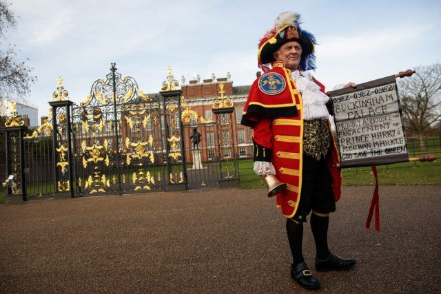 Tony Appleton dressed as a town crier poses with an announcement of Prince Harry and Meghan Markle's engagement
