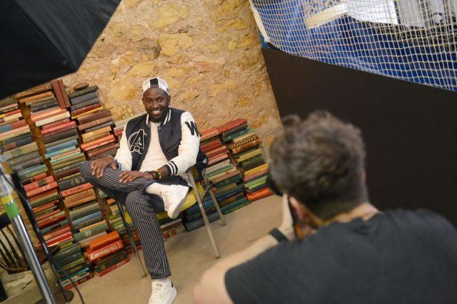 Anwan Glover sitting and posing during a photoshoot.
