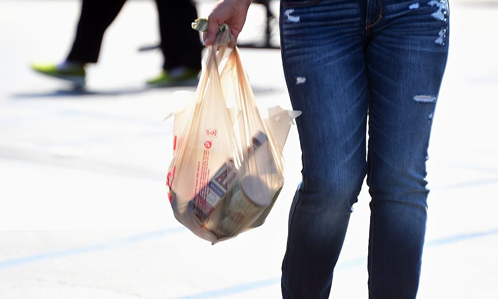 A woman carries her groceries in a plastic bag