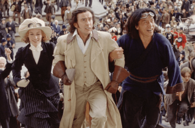 Three characters walking arm in arm in front of a large crowd.