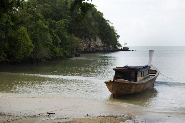 Asian thai people stop wooden motor boat on the beach