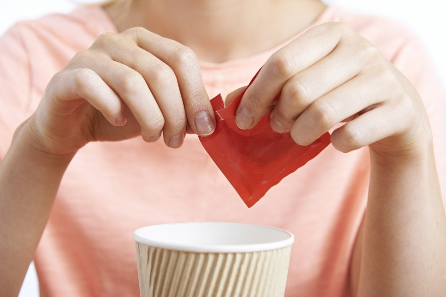 Woman adding artificial sweetener to her coffee