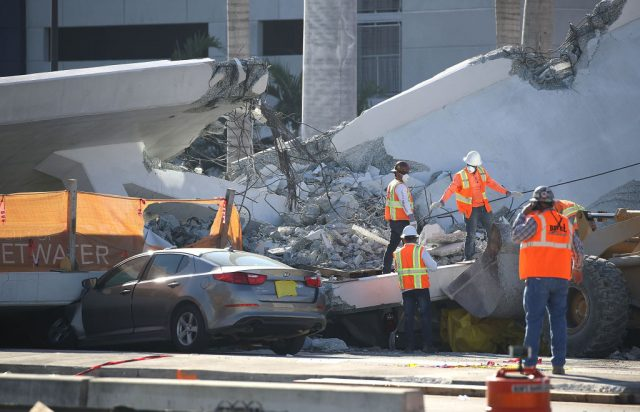 Workers, law enforcement and members of the National Transportation Safety Board investigate the scene where a pedestrian bridge collapsed a few days