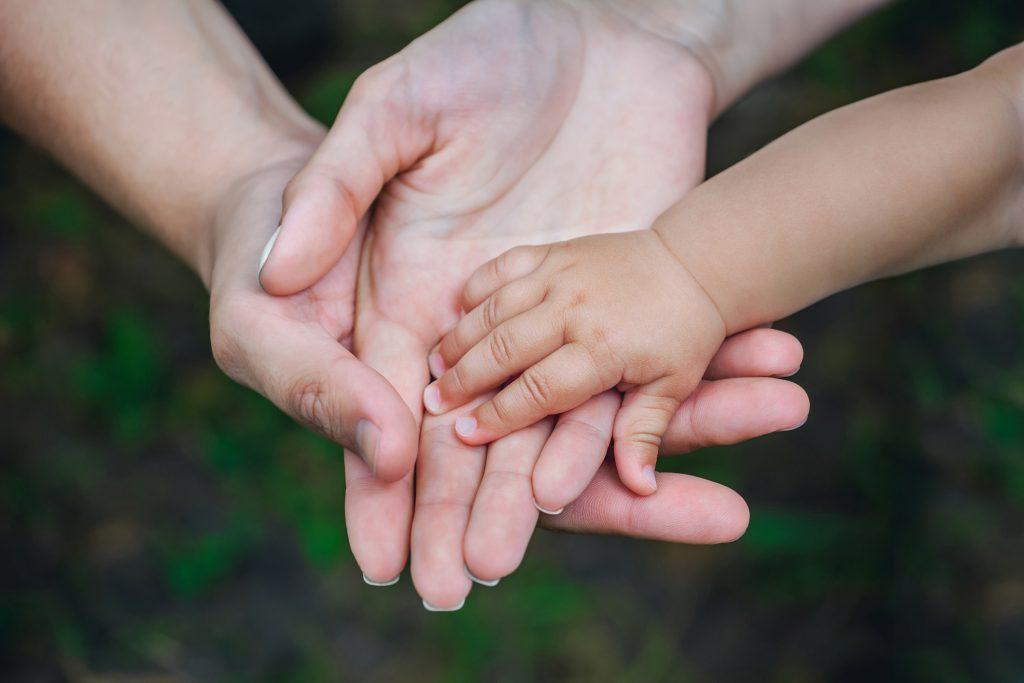 Parents' hands with baby