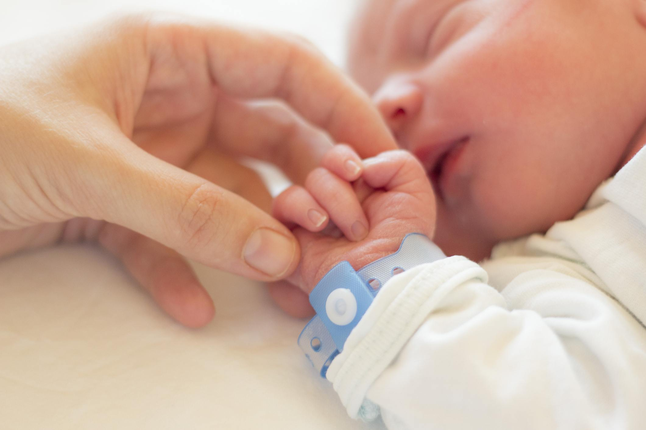 Newborn baby holding a hand