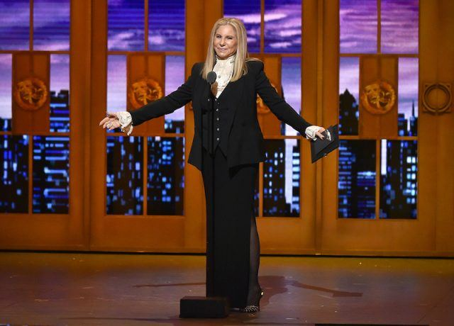 Barbara Streisand speaking on stage with her arms up.