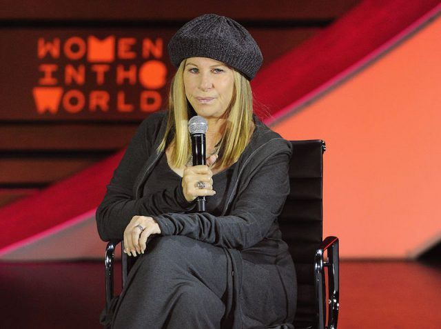 Barbara Streisand holding a microphone at a table.