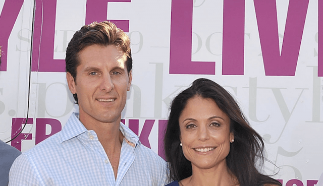 Bethenny Frankel and Jason Hoppy standing in front of a large truck.