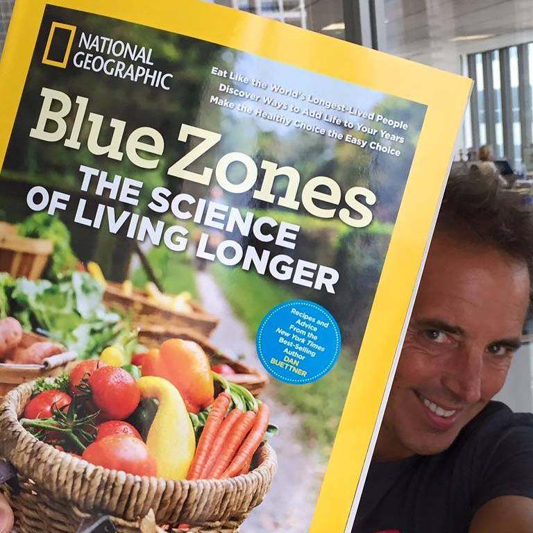 Man holding up a national geographic magazine saying Blue Zones Science of living longer