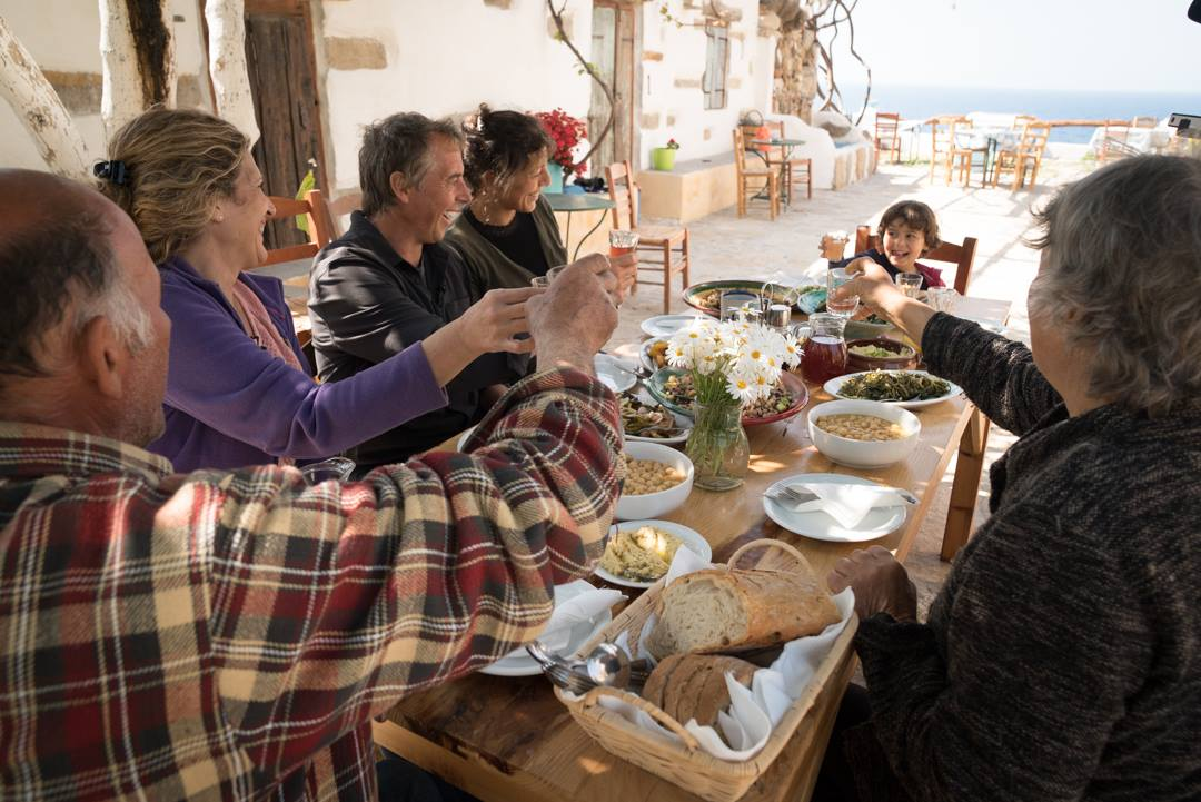 Family toasting around a table in Ikaria Greece