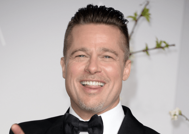 Brad Pitt smiling and sticking his tongue out.